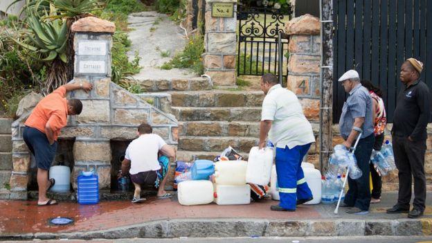 Люди собирают питьевую воду из труб, питаемых подземной весной, в Сент-Джеймс, примерно в 25 км от центра города, 19 января 2018 года, в Кейптауне.