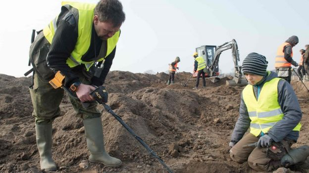 Amateur archaeologist Rene Schoen (L) and 13-year-old student Luca Malaschnichenko look for a treasure with a metal detector in Schaprode, northern Germany on April 13, 2018