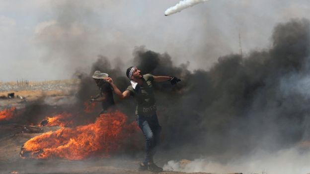 A Palestinian man uses a tennis racquet to return a tear-has canister fired by Israeli troops during a protest near the Gaza-Israel border fence (11 May 2018)