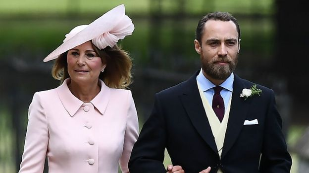 James Middleton, brother of the bride, walks with his mother Carole Middleton as they attend the wedding of Pippa Middleton and James Matthews