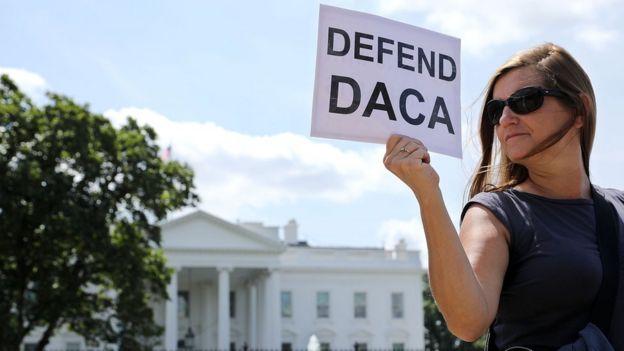 Mulher com cartaz com os dizeres Defenda DACA