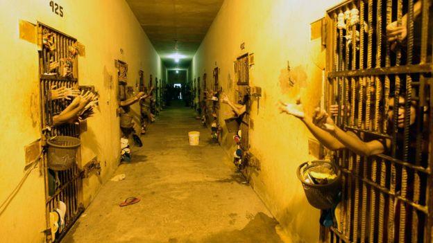 Corredor de presídio no Acre, com portas dos dois lados e braços para fora das celas