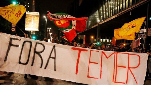 Manifestantes con pancartas que dicen