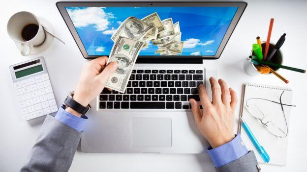 computadora con dinero volando.