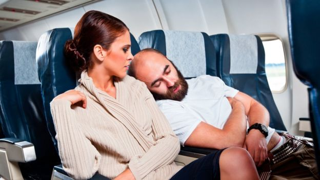 A man recharges on a woman's shoulder in an airplane