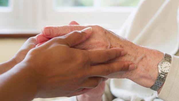 Una persona tomando de las manos a otra persona de mayor edad