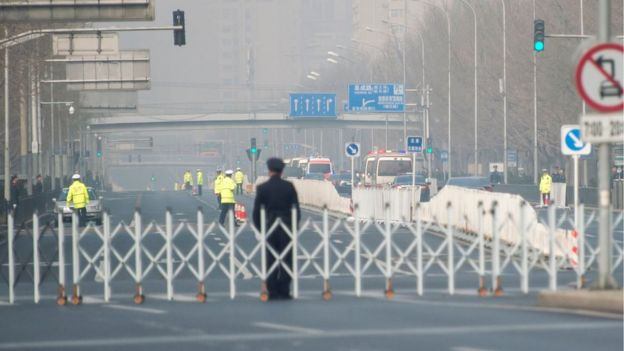Chinese policemen block a road as a procession believed to be North Korean officials pass near Diaoyutai State Guesthouse in Beijing