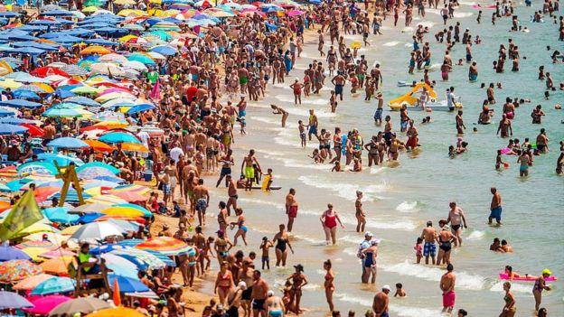 People sunbathe at Levante Beach in Benidorm, Spain