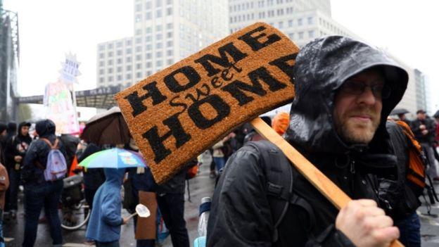 Homem segura placa escrita em inglês lar doce lar em protesto contra aumento do preço do aluguel em Berlim em abril de 2018