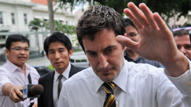 Swiss software consultant Oliver Fricker tries to avoid the media as he walks to the Subordinate court in Singapore on June 24, 2010.