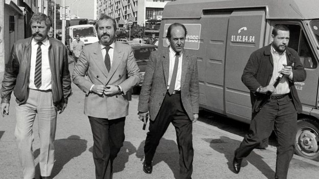 Judge Giovanni Falcone (second from left), surrounded by armed bodyguards, arrives 21 October 1986 in Marseille, France
