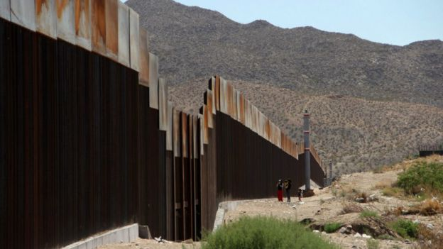 Una familia mexicana junto al muro que separa la frontera entre Estados Unidos y México en Tijuana.