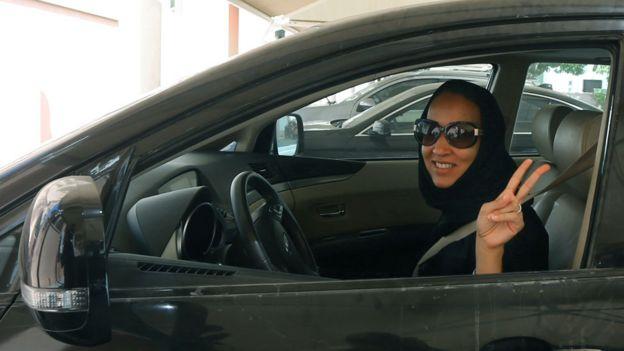 Mujer cubierta con ropas tradicionales conduciendo un auto y haciendo el símbolo V de victoria con su mano