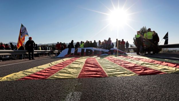 A Catalan flag is seen on the A-2 motorway as protesters block a road during a strike in Odena, Barcelona