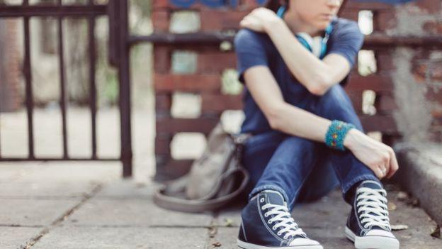 Adolescente sentada no chão