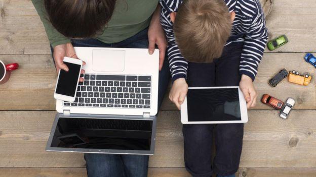 madre y niño usando laptop