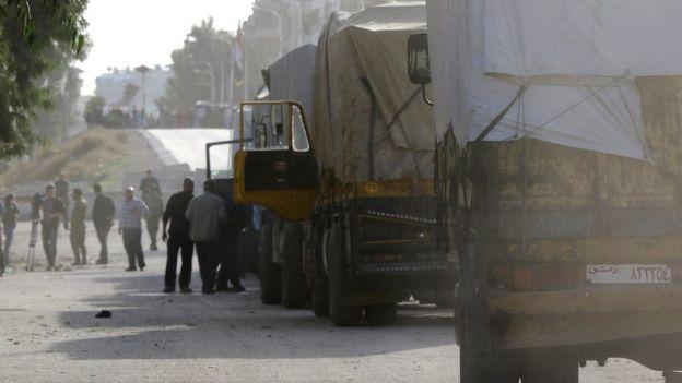 Грузовики ООН ожидают пропуска в городок Моадимайет-аш-Шам поблизости от Дамаска