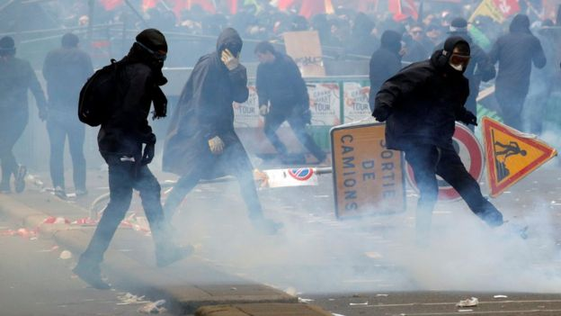 Tear gas floats around masked protesters during clashes with French CRS riot police at the May Day labour union rally in Paris, France 1 May 2018.