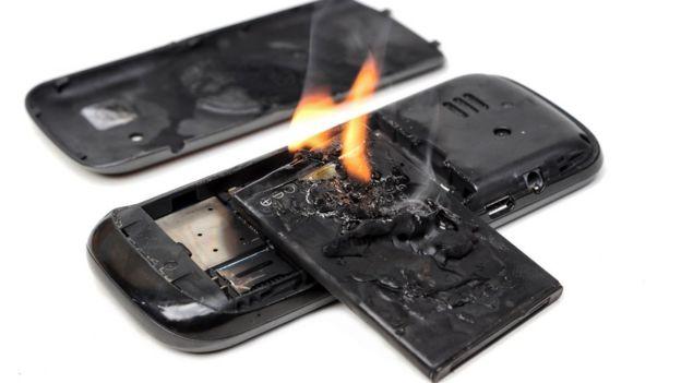 teléfono con la batería quemada y llamas saliendo.
