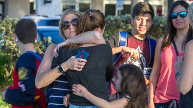 Familiares e crianças se abraçam nos arredores da escola pública Marjory Stoneman Douglas