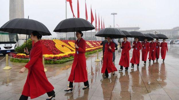 Asistentes al congreso con paraguas en la plaza Tianamén.