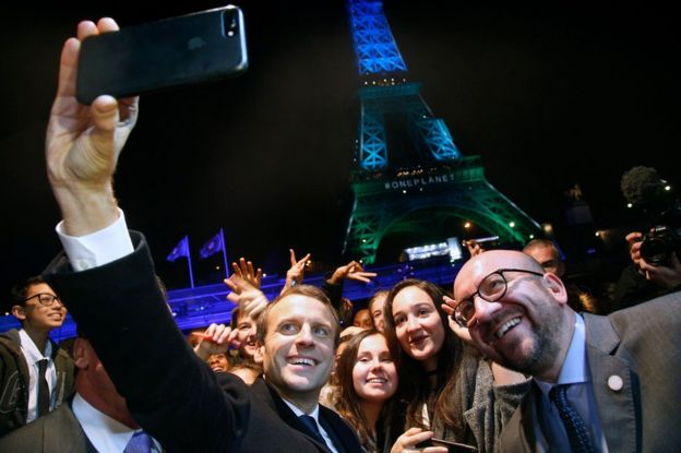 French president Emmanuel Macron uses his iPhone to take a selfie with the crowd in front of the Eiffel Tower