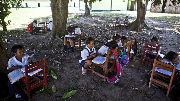 Niños en una escuela rural, estudiando sin carpetas.