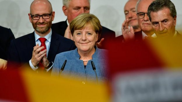 German Chancellor and Christian Democrat (CDU) Angela Merkel (C) reacts to initial results