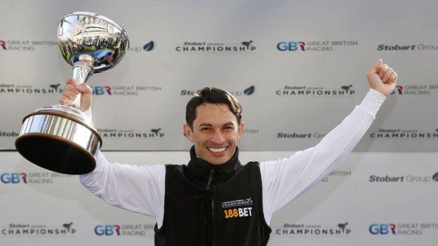 Silvestre de Sousa segura a taça de campeão