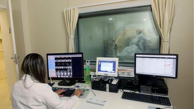 Profissional da saúde observa realização de tomografia