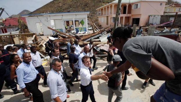 Emmanuel Macron da la mano a una residente de San Martín.