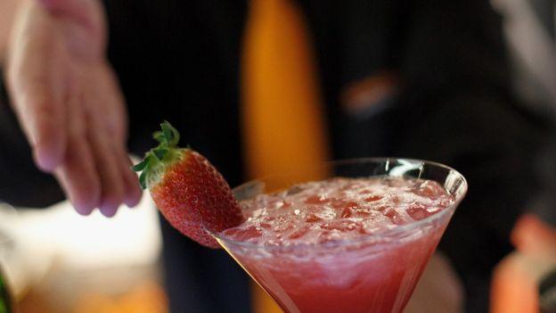 A bartender serves an Apache cocktail