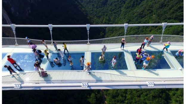 Visitors walk across a glass-floor suspension bridge in Zhangjiajie in southern China's Hunan Province Saturday, Aug. 20, 2016