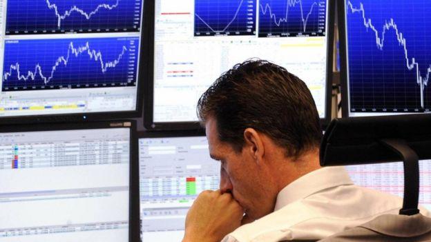Un hombre frente a pantallas que muestran la fluctuación de acciones en la bolsa de valores