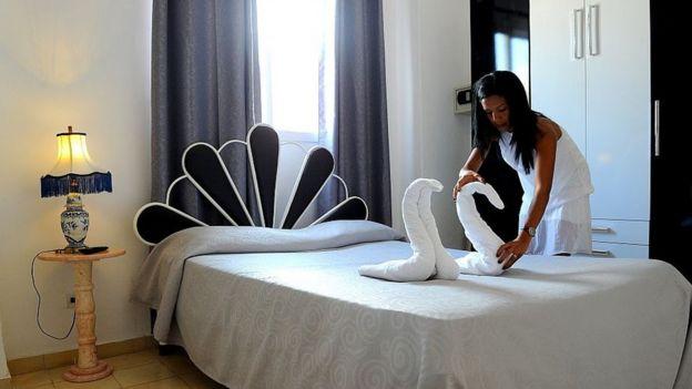Una mujer arregla unas toallas con formas de cisnes para dejarlas encima de una cama en una posada en La Habana.