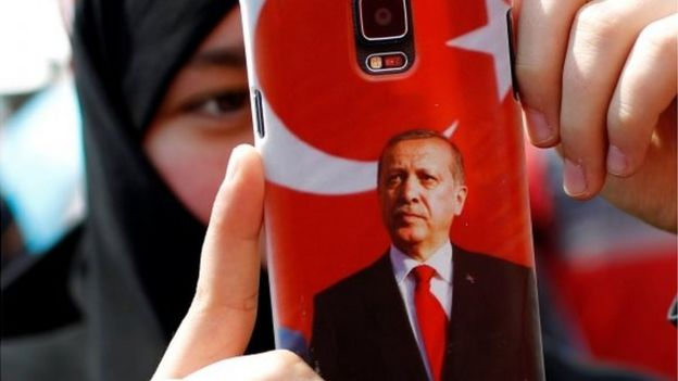 Una mujer toma una foto con un celular decorado con la imagen de Erdogan.