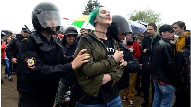 Policía rusa lleva detenida a una joven.