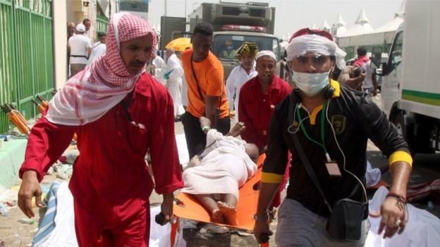 Saudi emergency personnel and Hajj pilgrims carry a wounded person at the site where hundreds were killed and wounded in a stampede in Mina