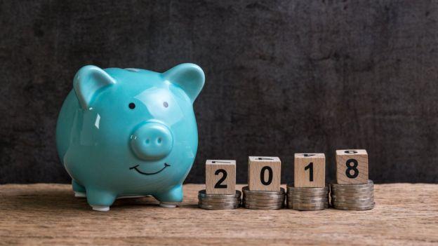 Cofre de porquinho azul à esquerda e cubos com os números do ano 2018 à direita