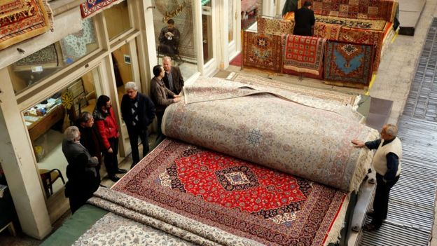 Shoppers and carpet sellers stand next to carpets in Tehran's Grand Bazaar in Iran.