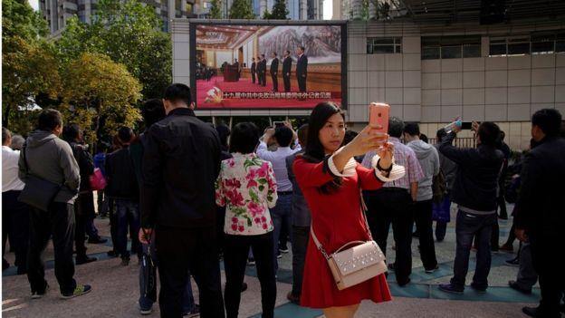在上海街頭上,很多民眾看政治局常委亮相的直播。