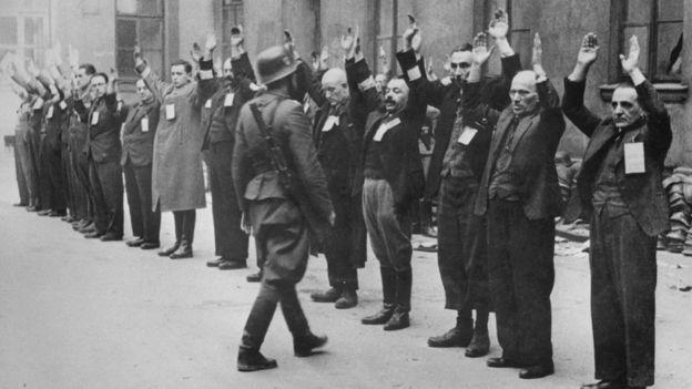 Soldado da SS inspeciona judeus no gueto de Varsóvia, na Polônia, em 1943