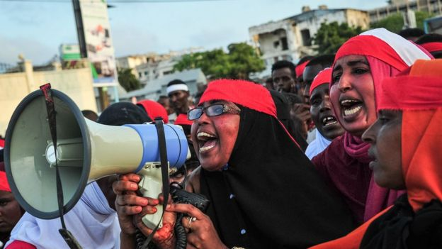 woman with red headband on shouting in to a megaphone