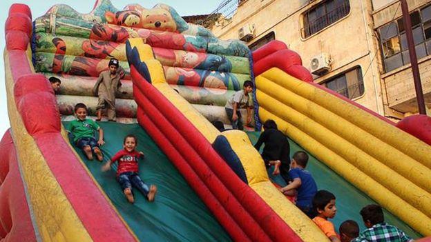 Дети катаются на надувной горке в городе Табка