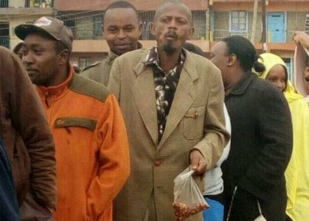'GitheriMan' standing in a queue with a bag of Githeri (cooked beans)