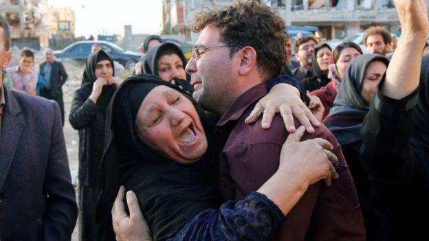 Una mujer y un hombre lloran junto a viviendas afectadas por el terremoto.