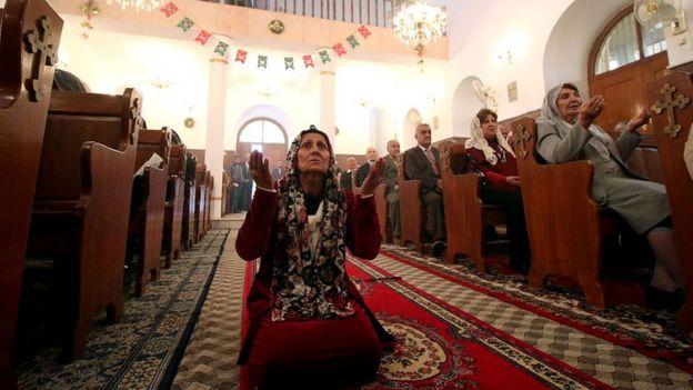 Una mujer reza en una iglesia católica en Irak.