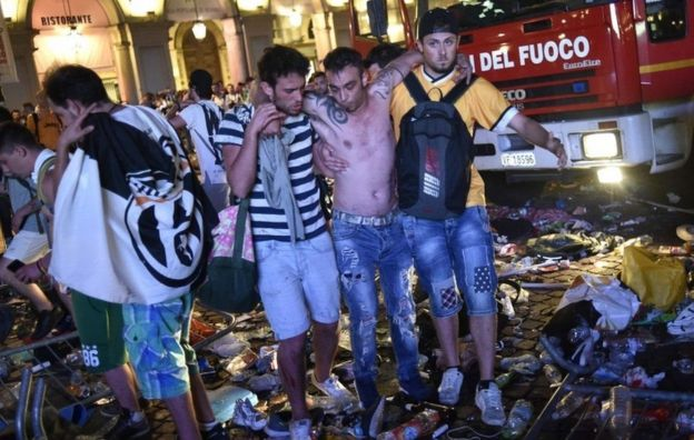 Herido saliendo de la plaza San Carlo, en Turín, con ayuda de dos personas.