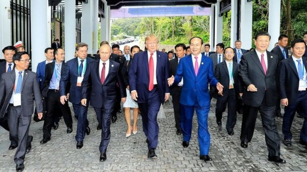 Donald Trump walks next to Vladimir Putin and other world leaders on the way to the
