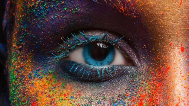 El ojo de una mujer y su cara pintada de diferentes colores.